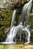 Kleiner schöner Wasserfall, der über graue Felsen fällt lizenzfreies stockfoto