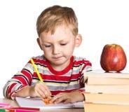 Kleiner Schüler, der durch seinen Schreibtisch sitzt Stockbild