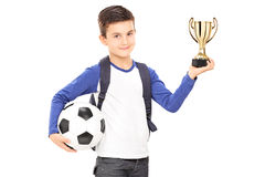 Kleiner Schüler, der Fußball und eine Trophäe hält Lizenzfreies Stockbild