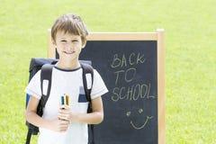 Kleiner Schüler mit Stiften und Rucksack gegen die Tafel Bildung, zurück zu Schulkonzept Lizenzfreies Stockbild