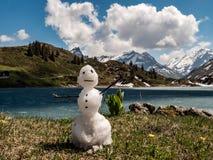 Kleiner Schneemann, der während des Frühlinges mit Gebirgslandschaft hinten schmilzt stockfotografie