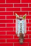 Kleiner Schrein zu den Erdgott Tu-Di brachte an einer roten Fliesenwand in Hong Kong an Lizenzfreies Stockfoto