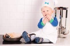 Kleiner Schätzchenchef im Kochhut, der Pfannkuchen bildet Stockfotos