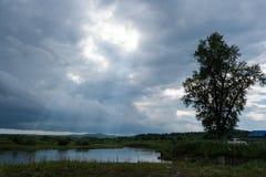 Kleiner See, fishermens und bewölkter Himmel mit Sonne strahlt aus lizenzfreie stockbilder