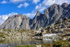 Kleiner See in hängendem Tal und in Bergspitzen lizenzfreie stockbilder