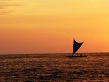 Kleiner Segelboots-Schattenbildsegelnhintergrund brannte orange Sonnenuntergang lizenzfreies stockbild