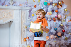 Kleiner sehr netter blonder Junge, der eine Geschenkbox über einen weißen Chris hält Lizenzfreie Stockbilder