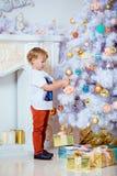 Kleiner sehr netter blonder Junge hängt oben den Ball auf weiße Weihnacht Stockfoto
