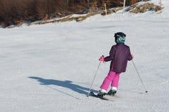Kleiner Skifahrer, der im Schnee läuft Stockfotos