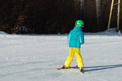 Kleiner Skifahrer, der im Schnee läuft Stockbilder