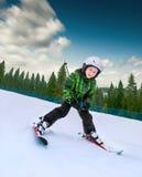 Kleiner Skifahrer, der unten vom schneebedeckten Hügel geht Lizenzfreie Stockbilder