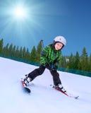 Kleiner Skifahrer, der unten vom schneebedeckten Hügel geht Stockbilder