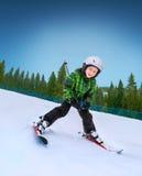 Kleiner Skifahrer, der unten vom schneebedeckten Hügel geht Stockfotografie
