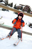 Kleiner Skifahrer sitzt auf Bretterzaun Stockfotografie