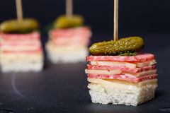 Kleiner Snäcke Canape mit Salami, Käse und Essiggurke auf Aufsteckspindel an stockfotografie