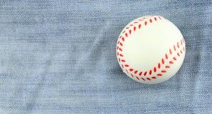 Kleiner Spielzeugbaseball auf Baumwollstoffhintergrund Lizenzfreies Stockbild