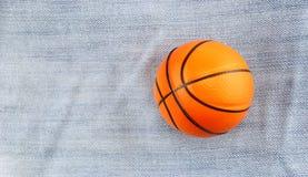 Kleiner Spielzeugbasketball auf Baumwollstoffhintergrund Lizenzfreie Stockbilder