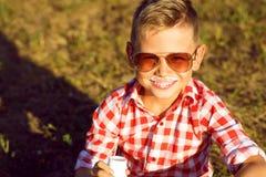 Kleiner stilvoller Junge in der Sonnenbrille sitzt auf dem Wiese drinki lizenzfreie stockfotos