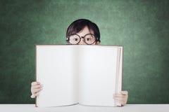 Kleiner Student zeigt leeres Buch im Klassenzimmer Lizenzfreie Stockbilder