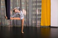 Kleiner Tänzer in einer Luftyogahängematte stockfoto
