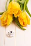 Kleiner Tasse Kaffee und gelbe Tulpen Stockfoto