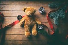 Kleiner Teddy Bear mit Weihnachtskiefernkegeln lizenzfreie stockfotos
