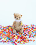 Kleiner Teddybär, der auf einem bunten Süßigkeitenbelag sitzt Weichzeichnung, heller Ton, Nahaufnahme Stockbild