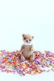 Kleiner Teddybär, der auf einem bunten Süßigkeitenbelag sitzt Weichzeichnung, heller Ton, Nahaufnahme Lizenzfreie Stockbilder