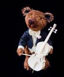 Kleiner Teddybär, der Cello spielt Stockfotos