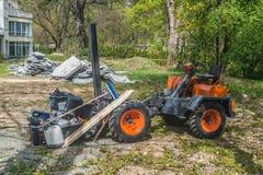Kleiner Traktor mit Gabelstapler während der Bauarbeiten lizenzfreie stockbilder