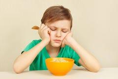 Kleiner unzufriedener Junge möchte nicht Getreide essen Stockfoto