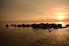 Kleiner Vogel, der auf einem Satz Felsen während des Sonnenaufgangs in Griechenland liegt lizenzfreies stockfoto