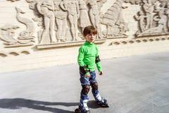Kleiner Vorschülerjunge, der Rollerskating lernt Stockbilder