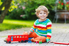 Kleiner Vorschuljunge, der mit Autospielzeug spielt Stockbild
