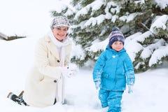 Kleiner Vorschuljunge und seine Mutter, die mit erstem Schnee in p spielt Lizenzfreie Stockbilder