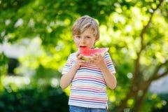 Kleiner Vorschulkinderjunge, der Wassermelone im Sommer isst Lizenzfreie Stockbilder