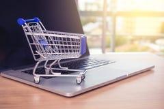 Kleiner Warenkorb auf Laptop für online kaufen mit sonnigem Hintergrund, Technologiegeschäfts-on-line-Konzept lizenzfreies stockbild