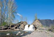 Kleiner Wasserfall auf einem Hintergrund des blauen Himmels Stockfotos