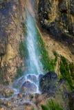 Kleiner Wasserfall auf in hohem Grade strukturiertem Felsen und Moos Stockbilder