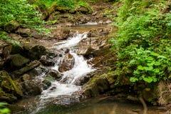 Kleiner Wasserfall in den Bergen Stockfotografie