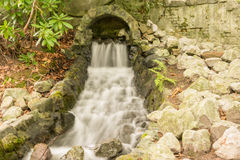 Kleiner Wasserfall, der aus Höhle herauskommt Stockbilder