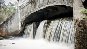 Kleiner Wasserfall, der von einer samll Verdammung fließt stockbild