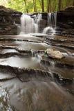 Kleiner Wasserfall mit überlagerten Felsen im Wald Stockfotografie