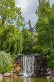 Kleiner Wasserfall mit Steinen und Mühle am Hintergrund stockfotos