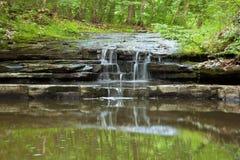 Kleiner Wasserfall tief im Wald Lizenzfreies Stockfoto