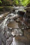 Kleiner Wasserfall tief im Wald Lizenzfreie Stockfotografie