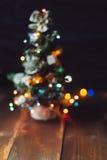 Kleiner Weihnachtsbaum unscharf auf dem Tisch Stockfoto