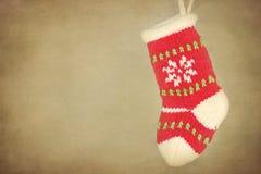 Kleiner Weihnachtsstrumpf, der am rustikalen Hintergrund hängt Lizenzfreie Stockfotografie