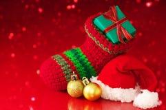 Kleiner Weihnachtsstrumpf und Sankt-Hut auf rotem Scheinhintergrund Stockfoto