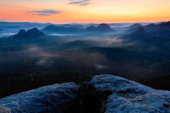 Kleiner Winterberg before sunrise, beautiful morning view over sandstone cliff into deep misty valley in Saxony Switzerland, foggy Stock Photos